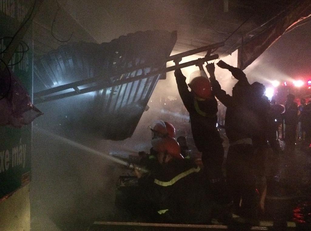 Cảnh sát PCCC phá cửa cuốn để dập lửa từ phía trong cửa hàng.