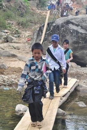 Học sinh địa phương đi trên chiếc cầu gỗ vừa mới được bắc tạm qua con suối tang thương