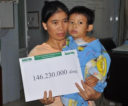 Mẹ con bé Thùy Dương nhận quà bạn đọc Dân trí.