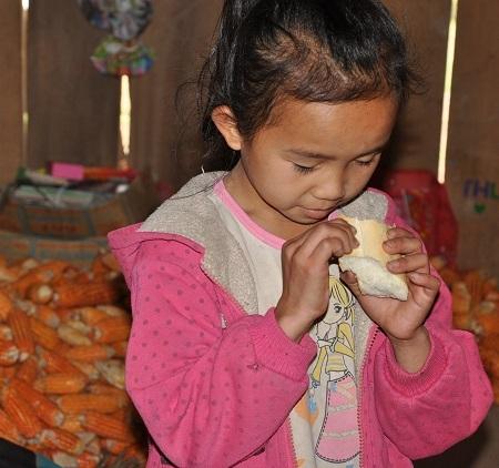 Cô bé út Triệu Thị Thu mừng rỡ khi được cho mẩu bánh mì.