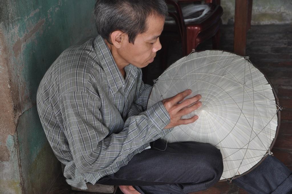 Hàng ngày anh Sơn ngồi cặm cụi khâu nón kiếm tiền cho vợ đi viện.