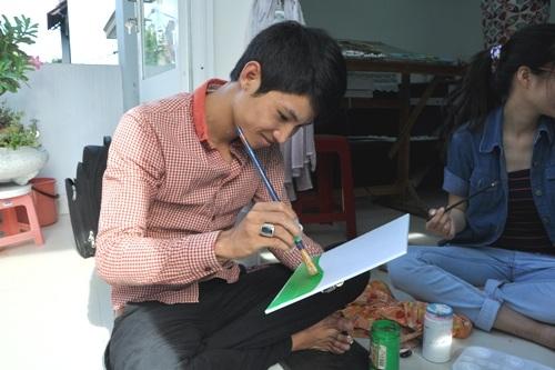 Nam đang vẽ nền trên giấy phom cho bức tranh của mình