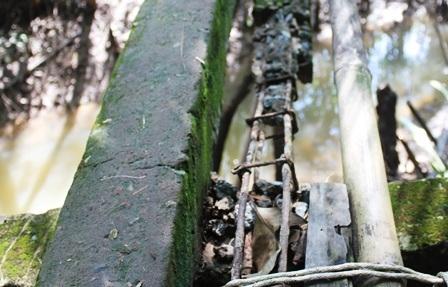 Mặt cầu làm bằng trụ cột nhà đã bị hư hỏng, bong tróc lộ ra thanh sắt.