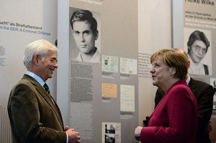 Bà Merkel trò truyện với một quan chức tại triển lãm.