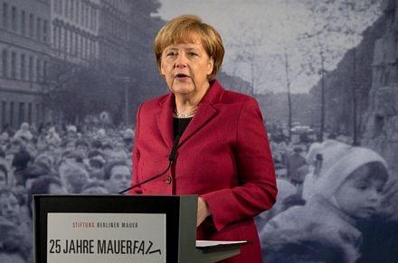 Bà Merkel gài hoa lênđoạn tường của Bức tường Berlin.