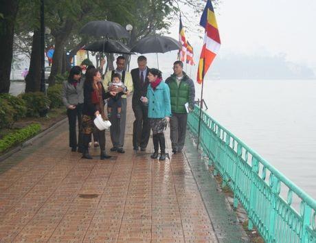 Đại sứ Mỹ và gia đình di dạo bên Hồ Tây trong tiết trời mưa nhỏ. (Ảnh: