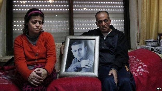 Cha mẹ của Musallam bên bức ảnh của con trai (Ảnh: