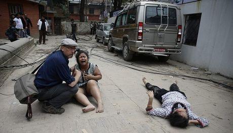 Một phụ nữ gào khóc bên cạnh một người khác bị thương sau động đất (Ảnh: AP)