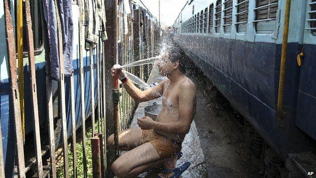 Một hành khách đi tàutắmđể hạ nhiệt tại gaởJammu (Ảnh: