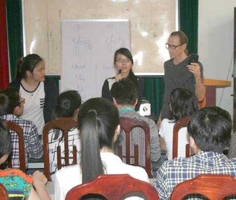 Thầy Paul lắng nghe và uốn nắn phát âm cho một nữ học viên trung niên.