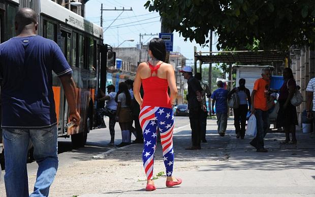 Một phụ nữmặc trang phục tái hiện quốc kỳ Mỹ trên đường phố Havana (Ảnh: AFP)