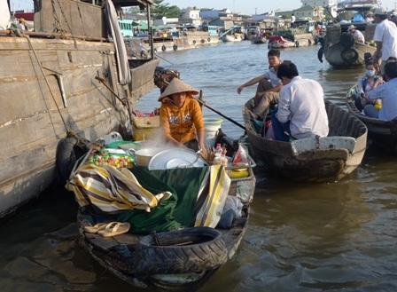 Một du khách thưởng thức tô bún riêu nóng hổi ngay trên sông
