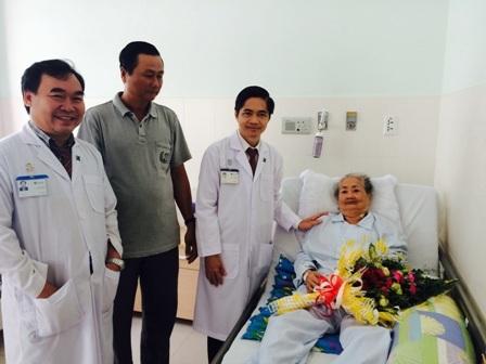 Lãnh đạo bệnh viện và bác sĩ Ngô Đức Hải đến thăm, tặng hoa cho cụ Nương khi cụ được xuất viện