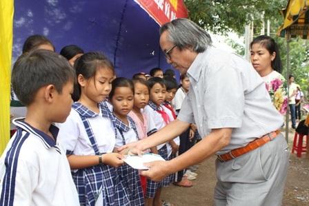 Nhà báo Phan Huy - Trưởng VPĐD báo Dân trí Khu vực ĐBSCL cùng trao học bổng cho các em học sinh