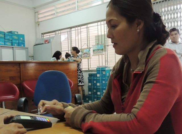 Ngành giáo dục TPHCM đang thực hiện lộ trình sử dụng thẻ học đường để tiến tới việc 100% thu học phí qua thẻ (Trong ảnh: Phụ huynh học sinh Trường THPT Tân Phong, Q.7 đóng học phí qua thẻ)