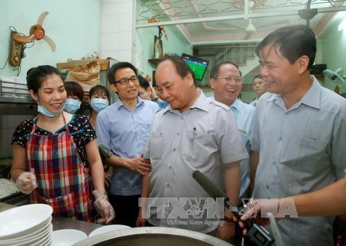 Thủ tướng tìm hiểu về quy trình nấu phở tại quán (Ảnh TTXVN)
