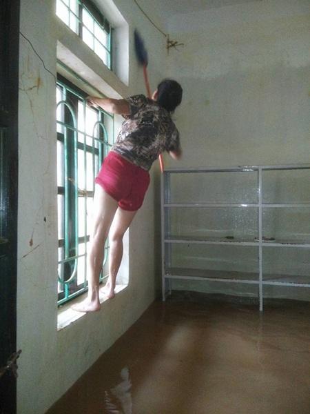 Bị bệnh cao huyết áp, nhưng cô Oanh vẫn cố sức trèo, lau dọn bùn đất bám trên tường.