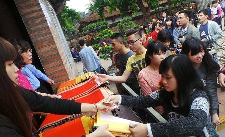 Xếp hàng mua giấy, nhận số thứ tự để chuẩn bị bước sang khu vực các ông đồ viết chữ.