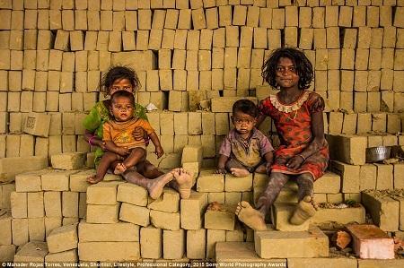 Hai cô bé sống trong khu ổ chuột ở Bangladesh đang thích thú tắm mưa. (Ảnh: Ata Mohammad Adnan)