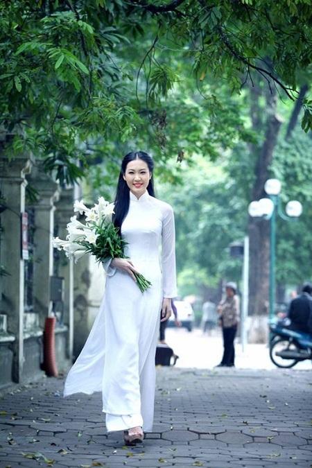 Á hậu Thùy Trang dịu dàng sải bước trên đường Hà Nội với bó hoa Loa kèn trên tay.