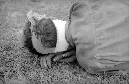 Đôi tay một người lính bị thương, đang nằm tựa đầu lên cánh tay.