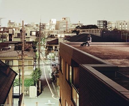 Một cô gái trẻ ngồi ngắm trời chiều trên tầng mái của một tòa nhà.