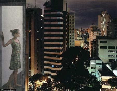 Một phụ nữ đứng bên cửa kính hướng mắt vào không gian thành phố ken đặc những tòa nhà cao tầng.