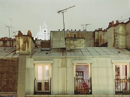 Người phụ nữ ngồi trên ghế với cửa sổ rộng mở đón gió đêm ở thành phố Paris, Pháp.