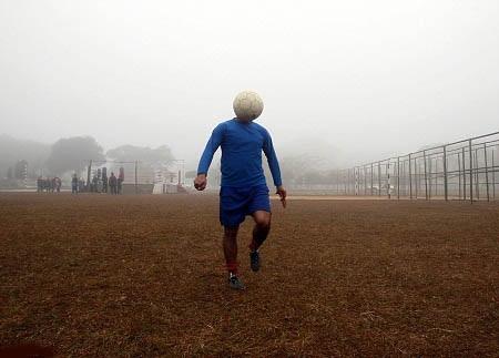 Một người đàn ông đang luyện tập với trái bóng trong buổi sáng mờ sương.