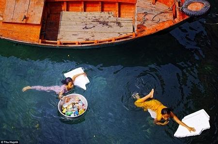 Hai cô bé đang bơi qua một con sông để nhặt những chiếc chai nhựa - Tác giả: Thu Huỳnh.