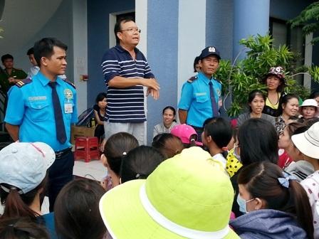 Ông Nguyễn Hữu Nghĩa (đứng, mặc áo sọc) thông báo trả lương chocông nhân(Ảnh: Phạm Thọ)