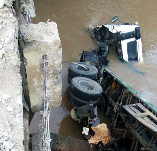 Sau khi đâm gãy lan can cầu, chiếc xe container rơi xuống suối.