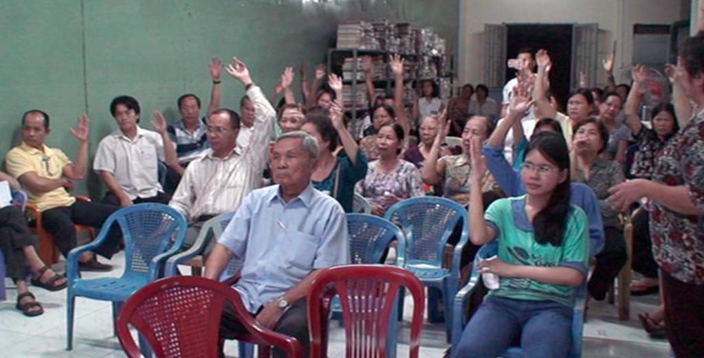 Cư dân chung cư giơ tay biểu quyết ý kiến thuê đơn vị quản lý bãi giữ xe mới trong hội nghị cư dân chung cư (ảnh cắt từ clip)