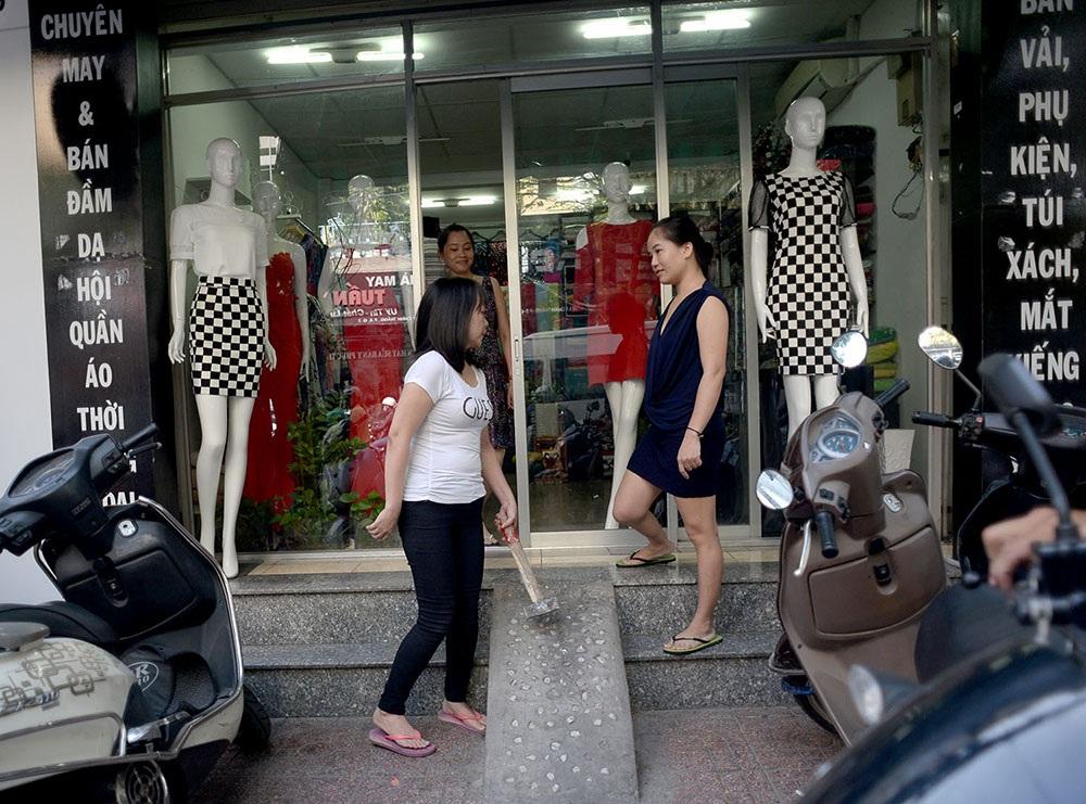 Hộ kinh doanh quần áo tại Quận 3 mang búa chuẩn bị đập bỏ phần xây dựng lấn chiếm.