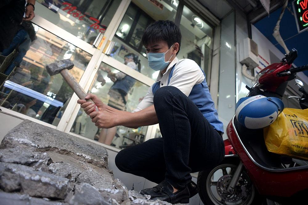 Nhân viên trong tiệm hớt tóc đường Lý Chính Thắng phá bỏ phần lối lên xuống trước cửa.