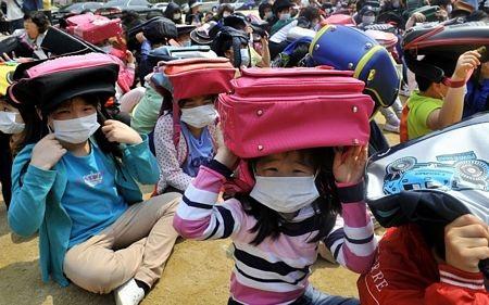 Các học sinh Hàn Quốc đội ba lô lên đầu trong cuộc diễn tập ứng phó động đất tại Seoul.
