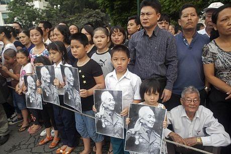 Người dân cầm di ảnh của Tướng Giáp khi chờ xe tang đi qua.