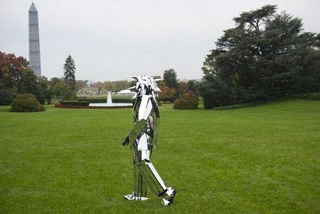 Một người biểu diễn mặc bộ đồlàm bằnggương đi lại trên bãi cỏ bên ngoài Nhà Trắng.