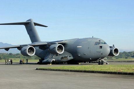 Các binh sĩ Mỹ đẩy một chiếc xe chở hàng cứu trợ được máy bay vận tải Mỹ đưa tới.