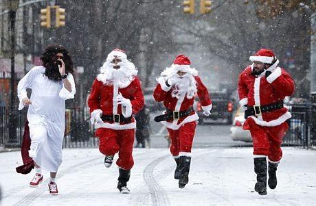 Các ông già Noel chạy dướitrời tuyết rơiở New York, Mỹ.