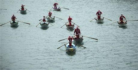 Mọi người hóa trang thành ông già Noel chèo thuyền ở Venice, Ý.