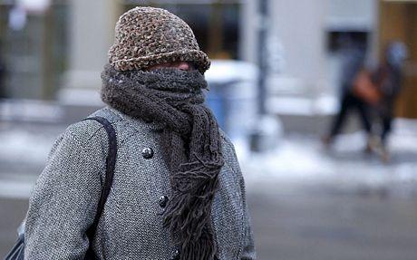 Một phụ nữ cố gắng giữ ấm bằng cách trùm kín người vàtrừ đôi mắt khi đi ra ngoài đường.
