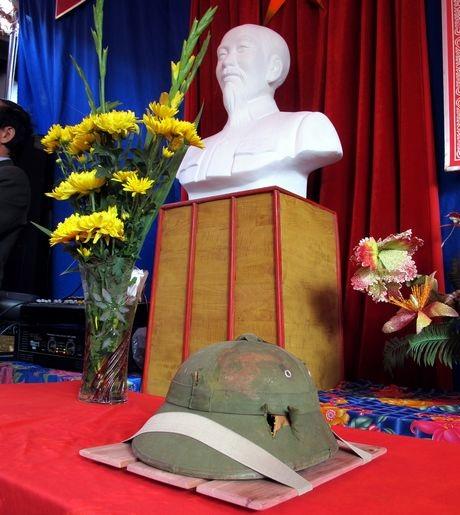 Chiếc mũ của liệt sĩ Bui Duc Hung được đặt cạnh tượng Bác Hồ trong lễ trao trả kỷ vật.