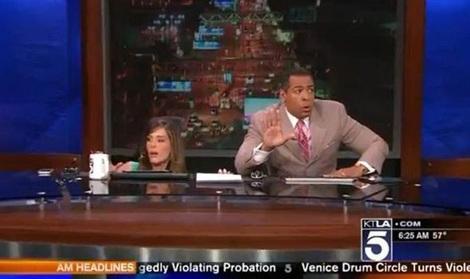 Hai người dẫn chương trình Chris Schauble và Megan Henderson nấp xuống gầm bàn để trú ẩn.