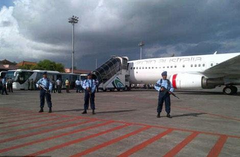 Lực lượng an ninh vây quanh chiếc máy bay hãng Virgin khi nó hạ cánh xuống sân bay Bali.