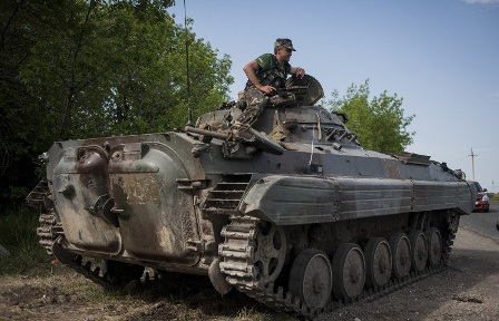 Xe tăng và binh sĩ Ukraine đứng chốt tại một trạm kiểm soát ở Mariupol. Ảnh: Itar-tass