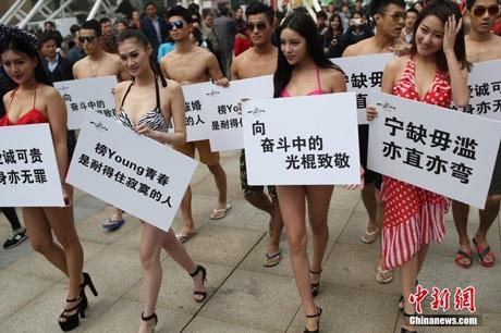 Các chàng trai cô gái trong trang phục kiệm vải giương tấm biển hiệu cổ động ngày độc thân tại TQ.