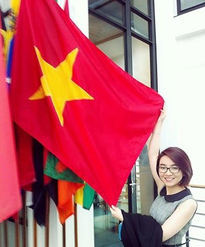 Phạm Ngọc Minh Trang tươi tắn bên lá cờ tổ quốc. (Ảnh do nhân vật cung cấp)