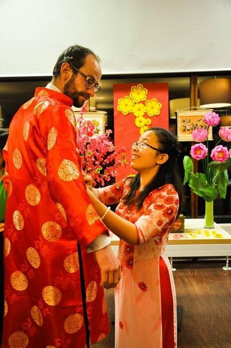 Cô gái Việt chỉnh áo dài giúp người khách Tây.