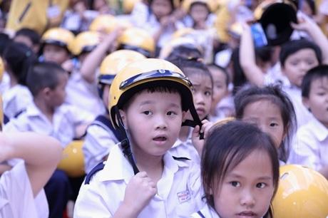Học sinh rất vui khi được đội mũ bảo hiểm